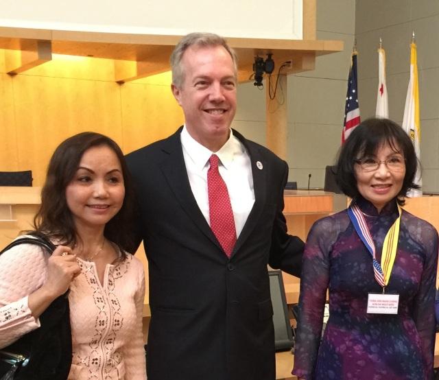 Cô Đỗ Minh Ngọc với dây đeo có cờ vàng chụp hình chung với Đại sứ Ted Osius sau buổi thảo luận